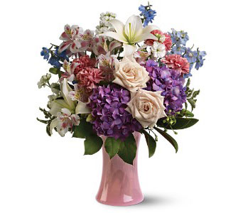 A mix of fresh flowers such as roses, delphinium, hydrangea and Asiatic lilies in shades of blue, purple, pink, white and crème - accented with greenery - is delivered in a glass vase From Plaza Flowers, your King of Prussia Florist.