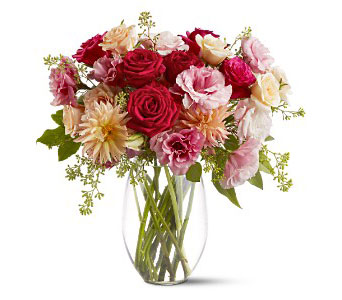 An assortment of fresh flowers such as roses, dahlias and lisianthus - in complementary shades of red, pink and peach - are delivered in a clear glass vase. From Plaza Flowers, your King of Prussia Florist.