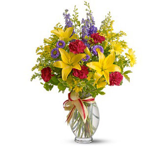 A mix of fresh flowers such as Asiatic lilies, larkspur, carnations and chrysanthemums - in shades of yellow, purple and red - is delivered in a clear glass vase decorated with yellow and red satin ribbons. From Plaza Flowers, your King of Prussia Florist.