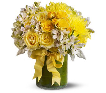 An assortment of fresh flowers such as roses, dahlias and stock, in shades of yellow, white and green, is arranged in a clear glass cylinder vase that's lined with leaves and decorated with a yellow ribbon. From Plaza Flowers, your King of Prussia Florist.